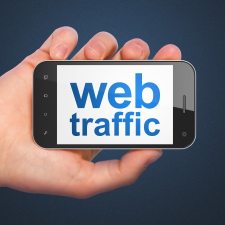 SEO web development concept: hand holding smartphone with word Web Traffic on display. Mobile smart phone in hand on Blue background, 3d render photo