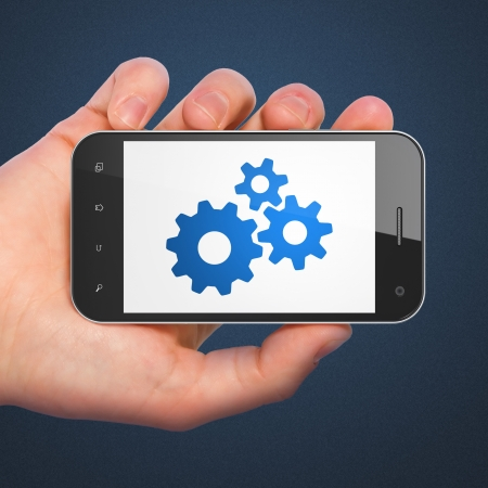 Web development concept: hand holding smartphone with Gears on display. Mobile smart phone in hand on Blue , 3d render photo