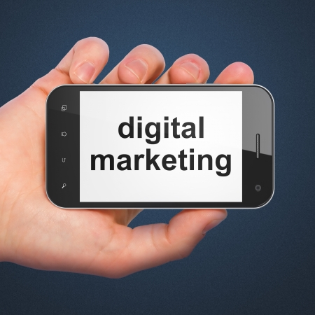 Marketing concept: hand holding smartphone with word Digital Marketing on display. Mobile smart phone in hand isolated on Blue , 3d render photo