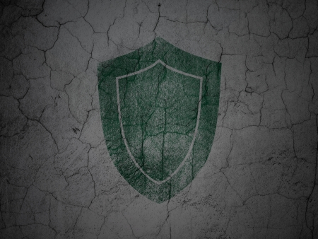 Safety concept: Green Shield on grunge textured concrete wall background, 3d render photo