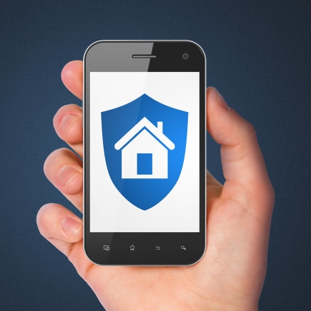 Safety concept: hand holding smartphone with Shield on display. Mobile smart phone in hand on Blue background, 3d render photo