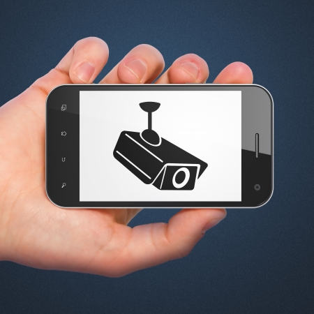 Safety concept: hand holding smartphone with Cctv Camera on display. Mobile smart phone on Blue background, 3d render photo