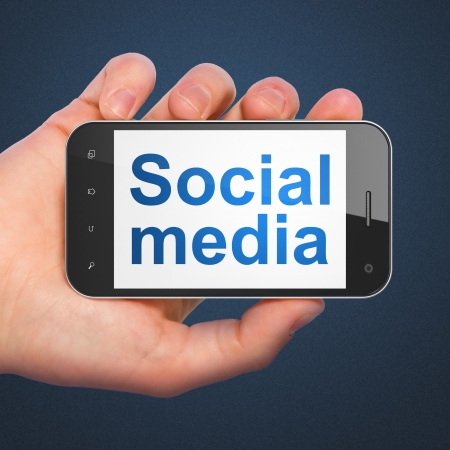 Social network concept: hand holding smartphone with word Social Media on display. Mobile smart phone on Blue background, 3d render photo