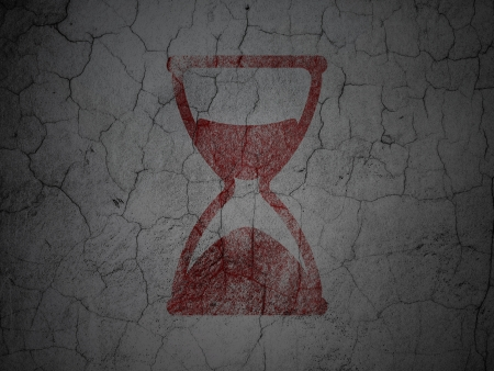 Timeline concept: Red Hourglass on grunge textured concrete wall photo