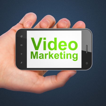 Business concept: hand holding smartphone with word Video Marketing on display. Mobile smart phone on Blue photo