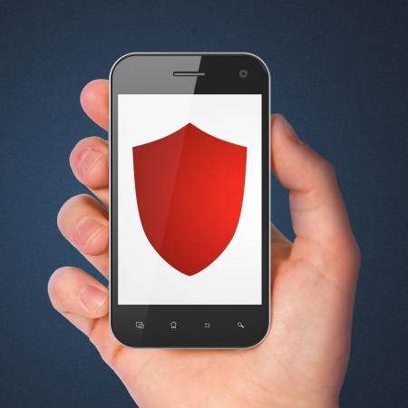 Security concept: hand holding smartphone with Shield on display. Mobile smart phone on Blue background, 3d render photo