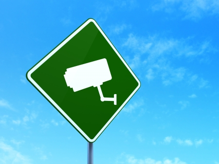 Protection concept: Cctv Camera on green road (highway) sign, clear blue sky background, 3d render photo