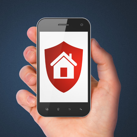 Safety concept: hand holding smartphone with Shield on display. Mobile smart phone on Blue background, 3d render photo