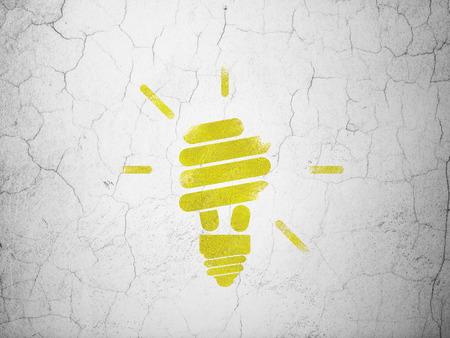 Business concept: Yellow Energy Saving Lamp on textured concrete wall background, 3d render photo