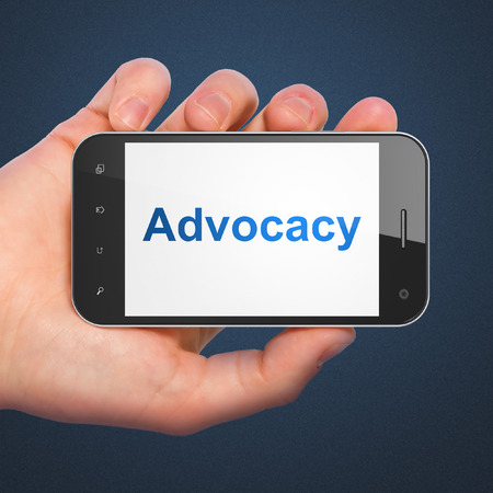 Law concept: hand holding smartphone with word Advocacy on display. Mobile smart phone on Blue background, 3d render photo