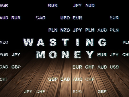 wasting: Banking concept: Glowing text Wasting Money in grunge dark room with Wooden Floor, black background with Currency Stock Photo