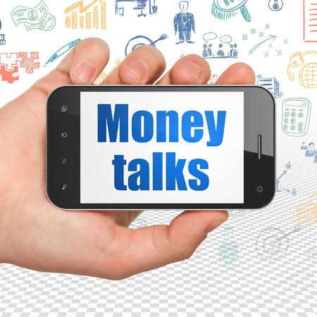 conversaciones: Concepto de las finanzas: Mano que sostiene el teléfono inteligente con el texto azul Money Talks en exhibición, dibujado a mano Iconos de negocios del fondo