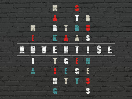 advertise: Marketing concept: Painted white word Advertise in solving Crossword Puzzle