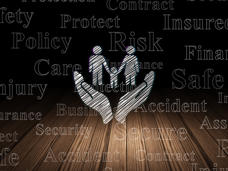 Insurance concept: Glowing Family And Palm icon in grunge dark room with Wooden Floor, black background with  Tag Cloud Stock Photo