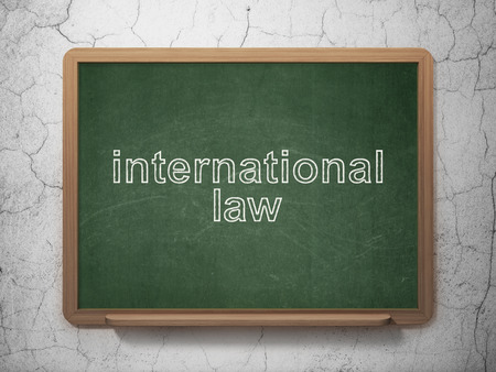 international law: Political concept: text International Law on Green chalkboard on grunge wall background