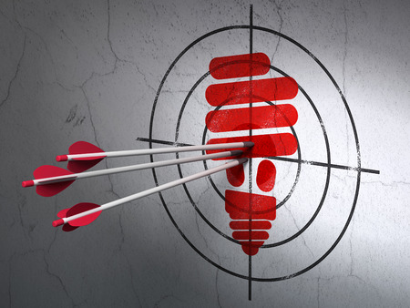 target shooting: Success business concept: arrows hitting the center of Red Energy Saving Lamp target on wall background