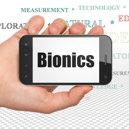 bionics: Science concept: Hand Holding Smartphone with  black text Bionics on display,  Tag Cloud background Stock Photo