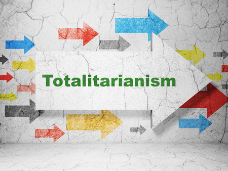 totalitarianism: Political concept:  arrow with Totalitarianism on grunge textured concrete wall background