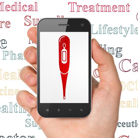 símbolo de la medicina: Medicina concepto: Mano que sostiene el tel�fono inteligente con el icono del term�metro rojo en la pantalla, Nube de etiquetas de fondo Foto de archivo