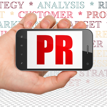 pr: Advertising concept: Hand Holding Smartphone with  red text PR on display,  Tag Cloud background