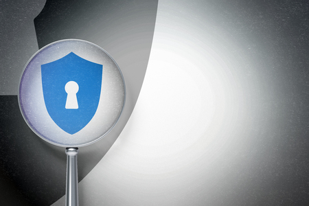 Privacy concept: magnifying optical glass with Shield With Keyhole icon on digital background, empty copyspace for card, text, advertising Stock Photo