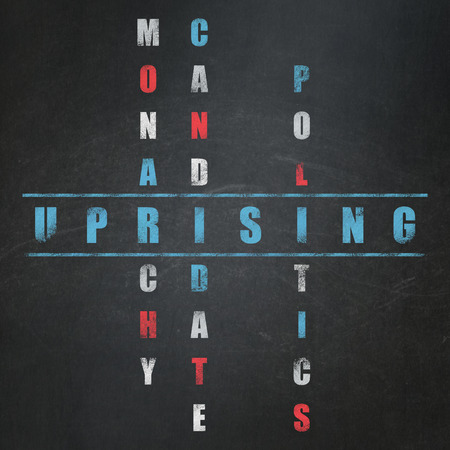 uprising: Political concept: Painted blue word Uprising in solving Crossword Puzzle on School Board background Stock Photo