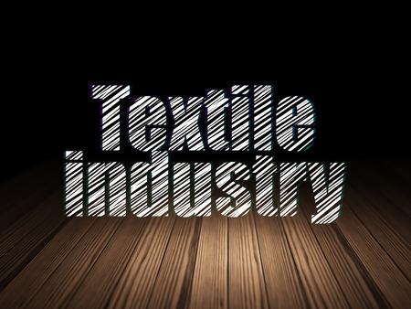 textile industry: concepto Manufacuring: Se ilumina en el texto de la Industria Textil en el grunge habitación oscura con el suelo de madera, fondo negro
