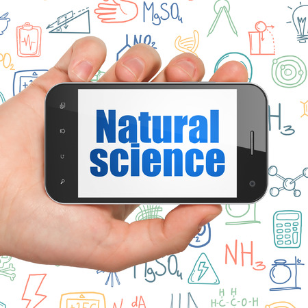 natural science: Science concept: Hand Holding Smartphone with  blue text Natural Science on display,  Hand Drawn Science Icons background