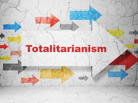 totalitarianism: Politics concept:  arrow with Totalitarianism on grunge textured concrete wall background