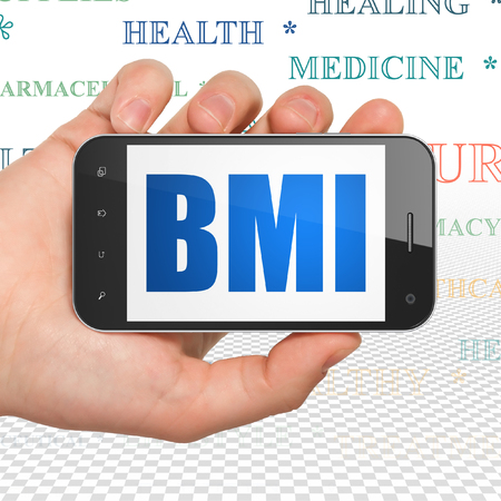 BMI: Medicine concept: Hand Holding Smartphone with  blue text BMI on display,  Tag Cloud background Stock Photo