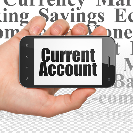 current account: Currency concept: Hand Holding Smartphone with  black text Current Account on display,  Tag Cloud background