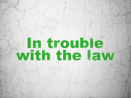 in trouble: Law concept: Green In trouble With The law on textured concrete wall background Stock Photo
