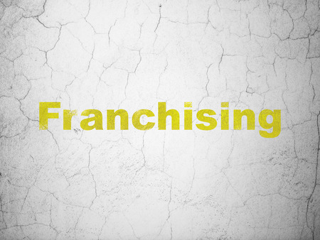 franchising: Finance concept: Yellow Franchising on textured concrete wall background