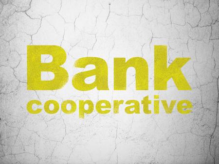 cooperativismo: concepto de moneda: Amarillo Banco Cooperativo en el fondo muro de hormigón con textura