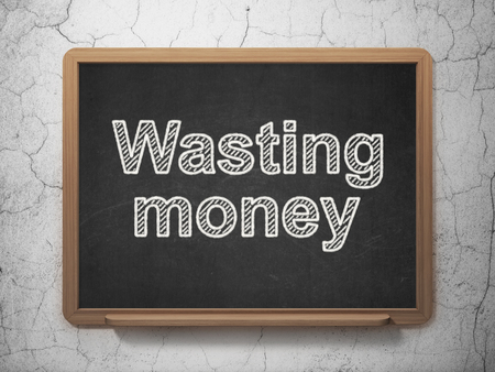 wasting: Money concept: text Wasting Money on Black chalkboard on grunge wall background, 3D rendering