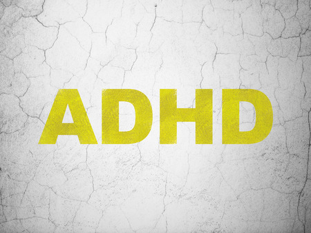 adhd: Health concept: Yellow ADHD on textured concrete wall background