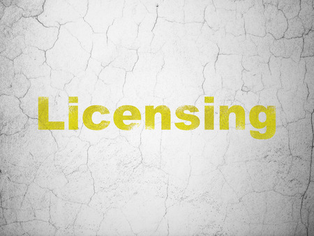 licensing: Law concept: Yellow Licensing on textured concrete wall background
