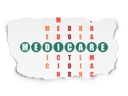 medicare: Health concept: Painted green word Medicare in solving Crossword Puzzle on Torn Paper background