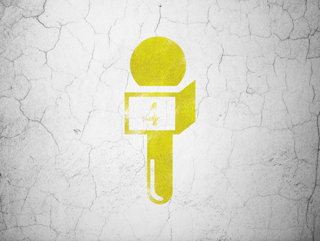 information age: News concept: Yellow Microphone on textured concrete wall background