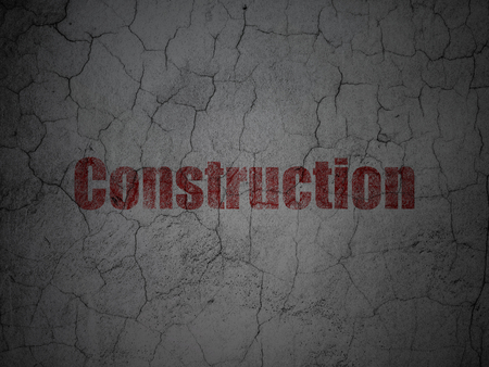 building site: Construction concept: Red Construction on grunge textured concrete wall background