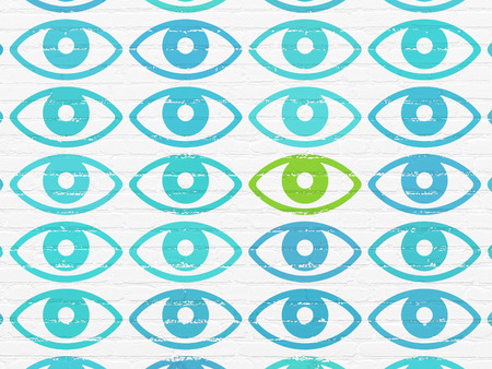 Safety concept: rows of Painted blue eye icons around green eye icon on White Brick wall background