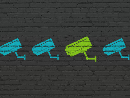 protect: Protection concept: row of Painted blue cctv camera icons around green cctv camera icon on Black Brick wall background Stock Photo