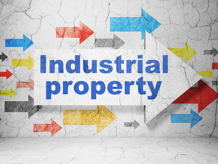 Law concept:  arrow with Industrial Property on grunge textured concrete wall background, 3D rendering Banco de Imagens