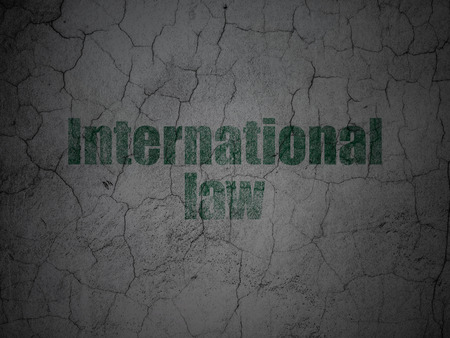 Political concept: Green International Law on grunge textured concrete wall background Stock Photo
