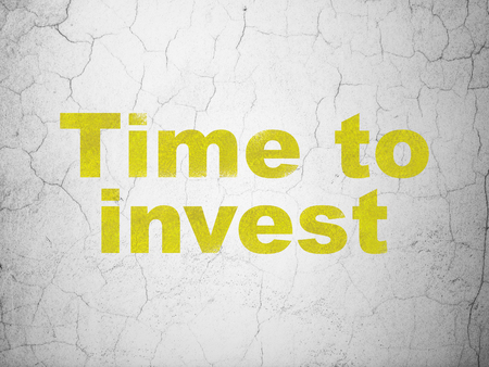 Timeline concept: Yellow Time To Invest on textured concrete wall background Stock Photo