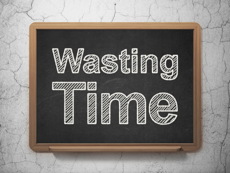 Time concept: text Wasting Time on Black chalkboard on grunge wall background, 3D rendering