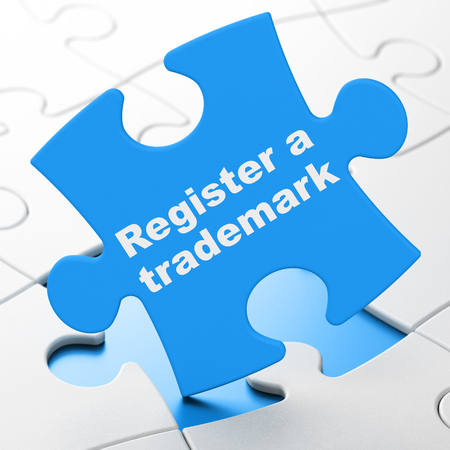 Concepto de ley: registrar una marca registrada en el fondo azul de piezas de un rompecabezas, representación 3D