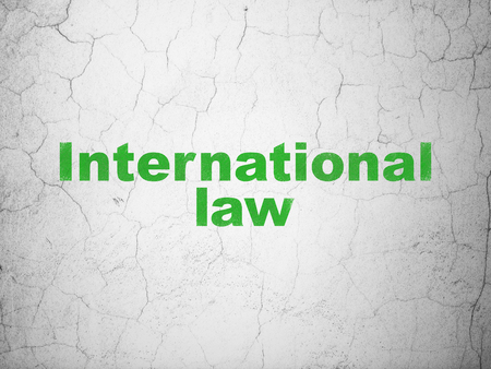 Political concept: Green International Law on textured concrete wall background Stock Photo