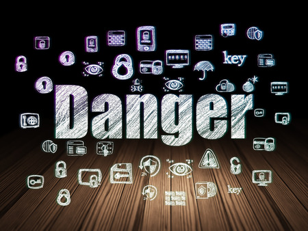 Safety concept: Glowing text Danger,  Hand Drawn Security Icons in grunge dark room with Wooden Floor, black background