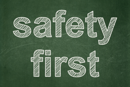 Protection concept: text Safety First on Green chalkboard background